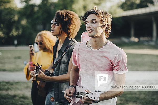 Junge Männer spielen Ukulele während sie an einem Musikfestival teilnehmen