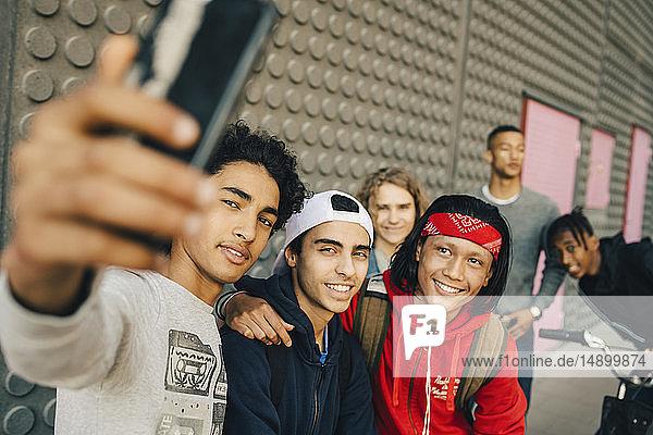 Happy male friends taking selfie with smart phone in city
