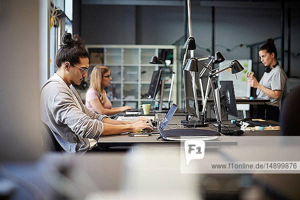 Männlicher Unternehmer mit Laptop am Schreibtisch im Kreativbüro
