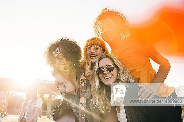 Fröhliche Freunde genießen bei sonnigem Wetter ein Musikfestival