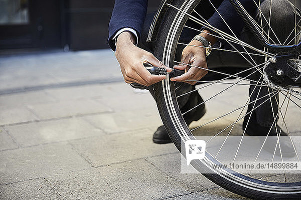 Low section of male commuter locking electric bicycle wheel against building in city