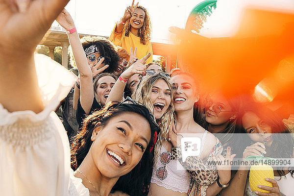 Hochwinkelansicht von fröhlichen Freunden  die im Sommer an Musikveranstaltungen teilnehmen Hochwinkelansicht von fröhlichen Freunden, die im Sommer an Musikveranstaltungen teilnehmen