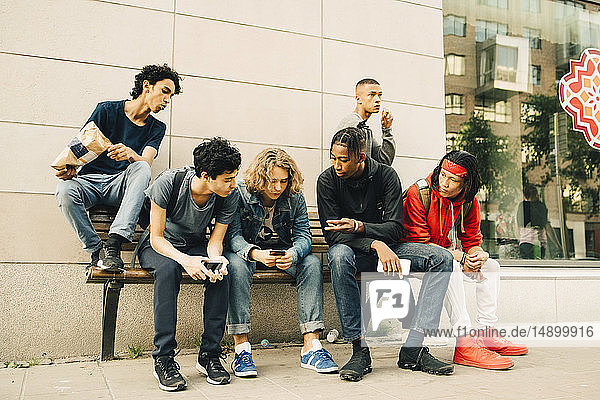 Males talking while sitting with friends on bench at sidewalk