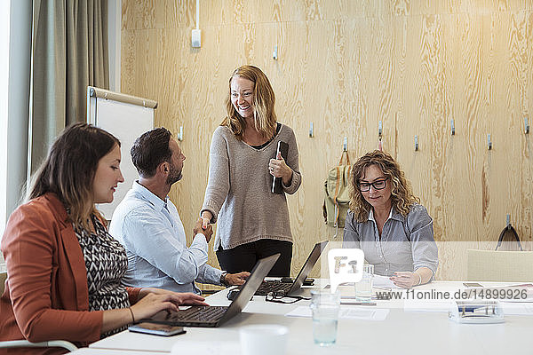 Smiling businesswoman shaking hand with businessman while female colleagues working at conference table