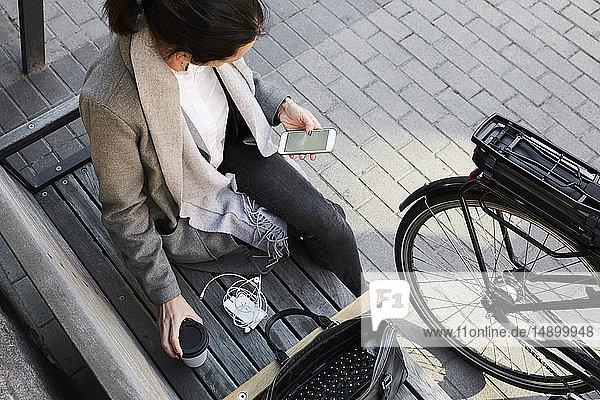 Schrägaufnahme einer Frau  die in der Stadt auf einer Bank sitzend per Mobiltelefon im Netz surft