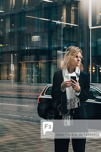 Businesswoman with smart phone looking away while standing on sidewalk against building in city