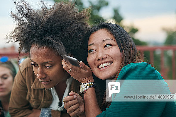 Freunde  die während des geselligen Beisammenseins auf der Terrasse Mobiltelefonen lauschen