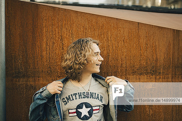 Cheerful young man holding denim jacket while looking away in city