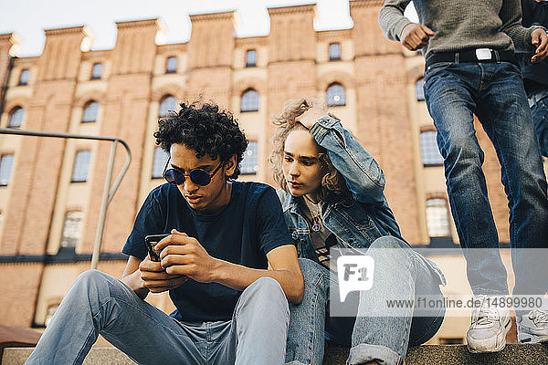 Teenage boy using mobile phone while sitting by friend in city