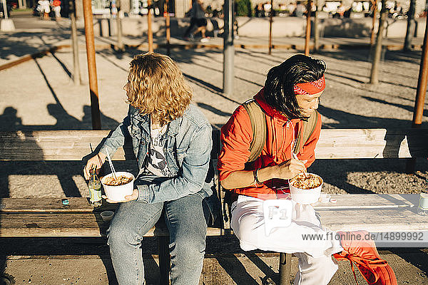 Friends eating take out food while sitting on bench in city during sunny day