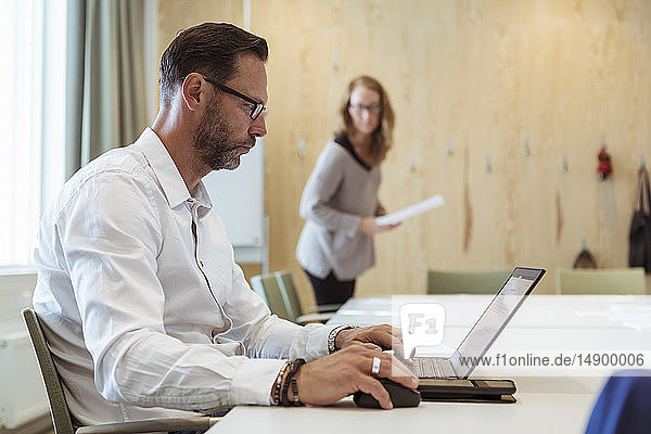 Serious businessman using laptop at conference table with female colleague in background