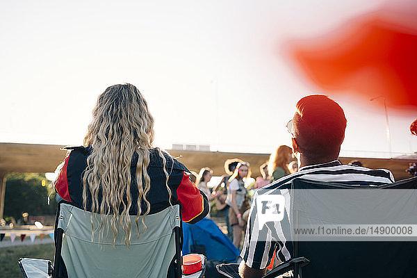 Rückansicht von Mann und Frau beim Blick auf die Darsteller beim Musikfestival