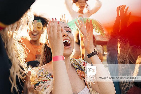 Weiblicher Fan schreit in der Menge beim Musikkonzert