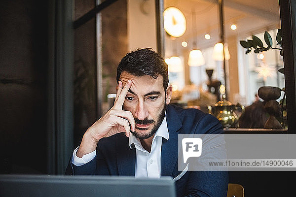 Tired businessman looking at laptop in creative office