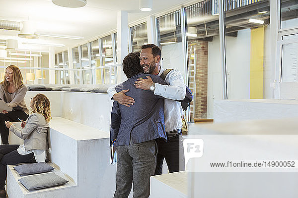 Smiling businessman embracing male colleague while standing in office