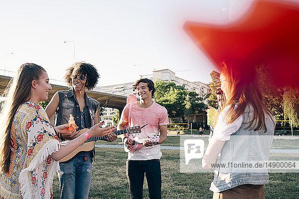 Freunde unterhalten sich während des Ukulele-Spiels beim Musikfestival im Sommer