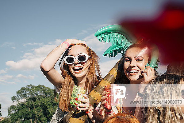 Fröhliche Freundinnen genießen Getränke bei Musikkonzert gegen den Himmel im Sommer