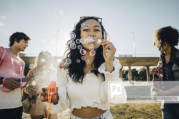 Frau bläst Seifenblasen  während Freunde während einer Musikveranstaltung Ukulele spielen
