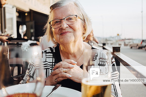 Smiling senior female tourist sitting with hands clasped at restaurant