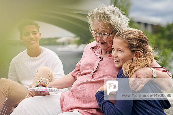 Smiling grandmother holding gifts while embracing granddaughter in park