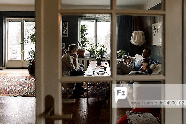 Family using various technologies in living room seen through transparent door at home