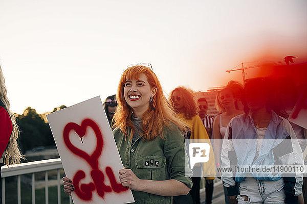 Lächelnde Frau mit Freunden marschiert für Frauenrechte in Stadt gegen Himmel