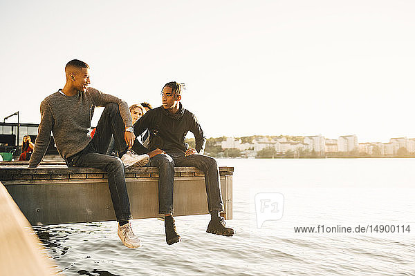 Full length of friends talking while sitting on pier over river against clear sky