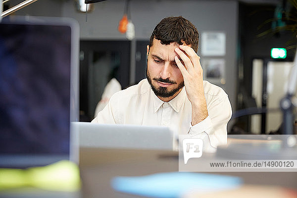 Stressed male entrepreneur looking at laptop while sitting in office