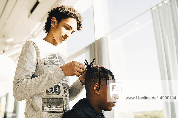 Teenage boy styling friend's hair while standing in restaurant