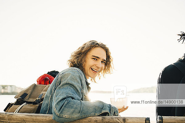 Portrait of cheerful young man holding meal in container while sitting by friend on promenade during sunny day