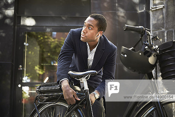 Young male commuter locking electric bicycle while looking away against building in city
