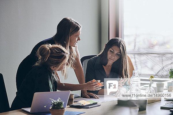 Zuversichtliche weibliche Fachleute planen Strategie über Dokumente während einer Sitzung im Sitzungssaal im Büro