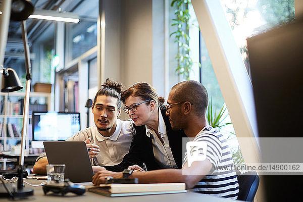 Male entrepreneurs explaining female bank manager over laptop at desk in creative office