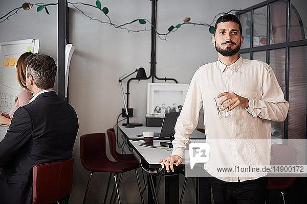 Nachdenklicher männlicher Unternehmer hält ein Trinkglas in der Hand  während er im kreativen Büro am Schreibtisch steht