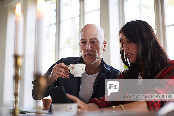 Mature woman showing mobile phone to male friend while sitting in dining room at home