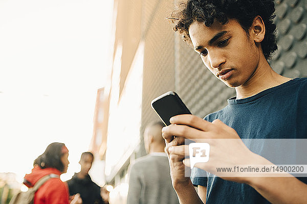 Teenage boy using mobile phone while friends standing in background on city street