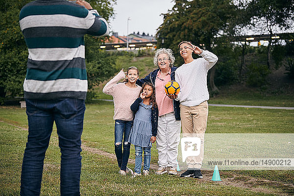 Midsection of man photographing happy grandmother and grandchildren gesturing peace sign in park during picnic