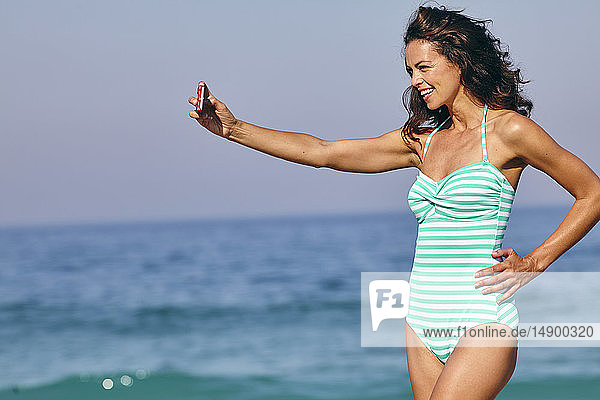 Beautiful bronzed woman in a striped swimsuit taking a selfie on her phone