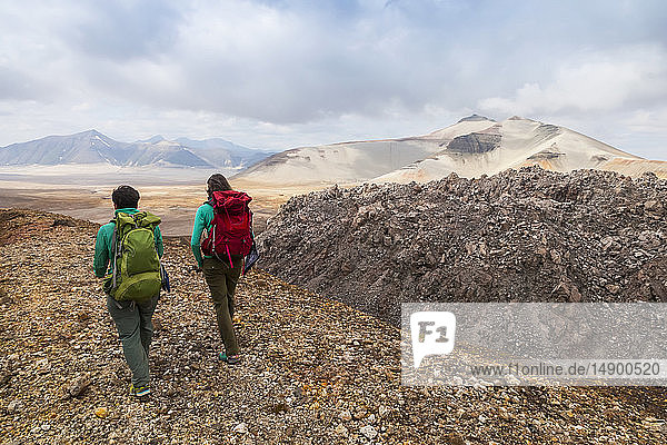 Two women backpacking past Novarupta with Baked and Broken Mountain in the background  Valley of Ten Thousand Smokes  Katmai National Park and Preserve  Southwest Alaska; Alaska  United States of America