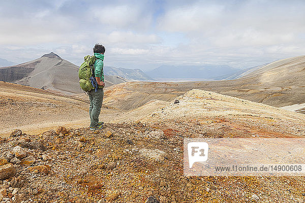 Woman backpacker viewing Baked Mountain in the distance in the Valley of Ten Thousand Smokes  Katmai National Park and Preserve  Southwest Alaska; Alaska  United States of America