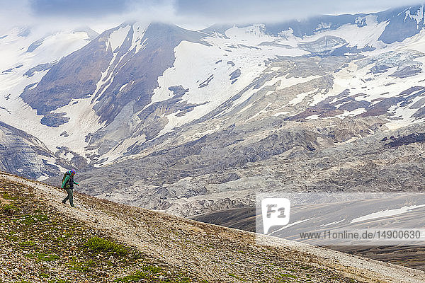 Woman backpacking down a slope with Mount Katmai in the background  Katmai National Park and Preserve  Valley of Ten Thousand Smokes  Southwest Alaska; Alaska  United States of America