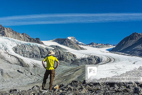 A man walks in Gulkana Glacier Valley in the Eastern Alaska Range in South-central Alaska on a sunny summer afternoon; Alaska  United States of America