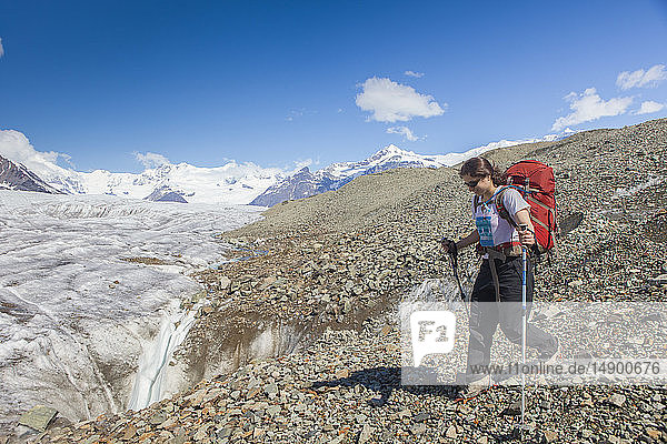 Woman backpacking on the Kennicott Glacier moraine headed towards the Kennicott Glacier  Wrangell Mountains  Wrangell-St. Elias National Park  South-central Alaska; Alaska  United States of America