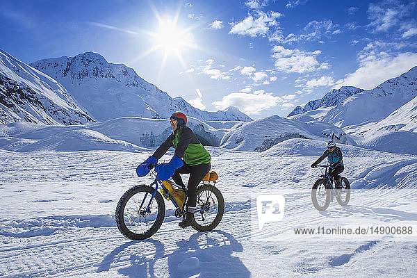 Two women fat biking in front of Skookum Glacier  Chugach National Forest  Alaska on a sunny winter day  South-central Alaska; Alaska  United States of America
