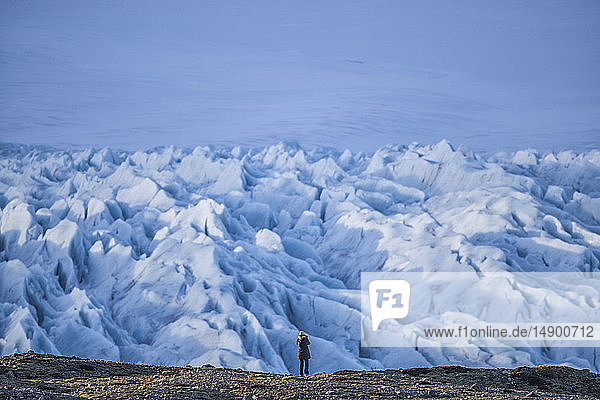 Person hiking and taking photos of a glacier along the South shore of Iceland; Iceland