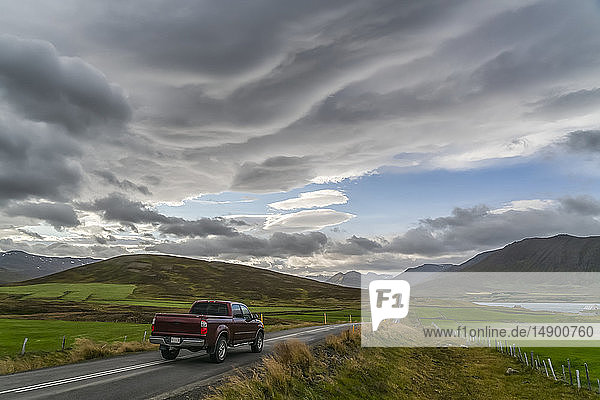 Pickup truck traveling on a road in the mountains; Iceland
