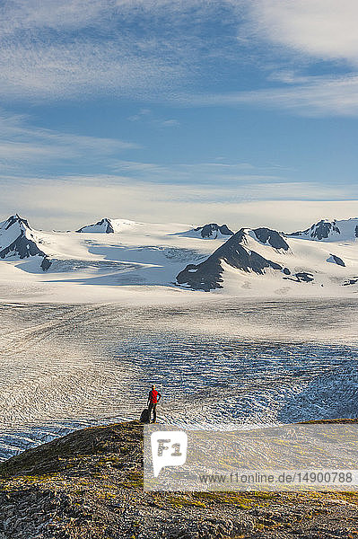 A man is seen standing next to his backpack while hiking the beautiful Harding Icefield Trail in Kenai Fjords National Park with the Harding Icefield in the background  Kenai Peninsula  South-central Alaska; Alaska  United States of America