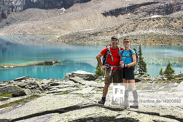 Female and male hiker standing in a large rocky area with colourful alpine lake and mountain cliffs in the background; British Columbia  Canada