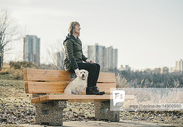 Woman out with her dog with a city skyline in the background; Edmonton  Alberta  Canada