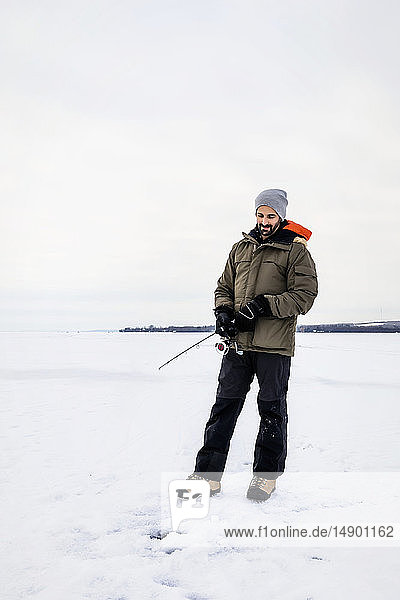 Man patiently waiting for a bite while ice fishing at Wabamun Lake; Wabamun  Alberta  Canada